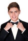 El hombre alegre en un traje negro ajusta su corbata de lazo Imagen de archivo libre de regalías