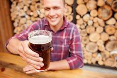 El hombre alegre está bebiendo a tragos la cerveza dorada en pub Fotos de archivo