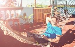 El hombre alegre joven miente resto de Cuba de la sol del patio de la hamaca Imagen de archivo