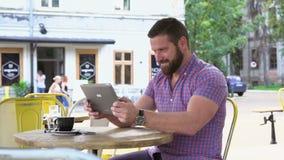 El hombre alegre que jugaba al juego en la tableta en el café, resbalador tiró a la derecha metrajes