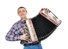 El hombre alegre toca la armónica Fotos de archivo