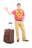 El hombre, alista por vacaciones, agitando con la mano Foto de archivo
