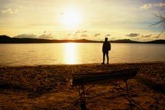 El hombre alto va a la costa del lago cerca de banco vacío de madera viejo El vintage entonó la foto imagenes de archivo