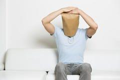 El hombre anónimo desgraciado con la cabeza cubrió sentarse en el sofá. Fotos de archivo libres de regalías