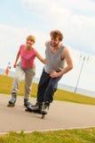 El hombre anima a la mujer a hacer rollerblading Imagen de archivo libre de regalías