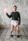 El hombre anormal divertido en pañal camina en casa abandonada imagenes de archivo