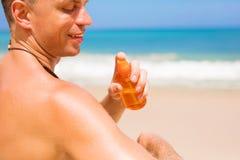 El hombre aplica la protección solar en su cuerpo en la playa fotografía de archivo libre de regalías