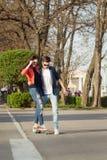 El hombre aprende a la novia para andar en monopatín Fotos de archivo