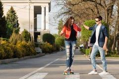 El hombre aprende a la novia para andar en monopatín Imagen de archivo