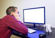 El hombre aprensivo mira fijamente el ordenador de oficina en maqueta negra de madera del escritorio Camisa roja punteada, pantal fotos de archivo libres de regalías
