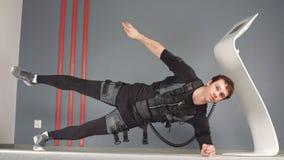 El hombre apto en el estímulo muscular eléctrico se adapta a hacer ejercicio lateral del tablón ems metrajes