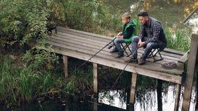 El hombre apuesto y su hijo lindo están pescando en la charca del muelle de madera que se sienta en sillas con las barras y habla almacen de metraje de vídeo