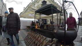 El hombre armenio prepara la comida en cocina al aire libre y la gente come almacen de video