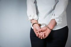 El hombre arrestado esposó las manos en la parte posterior en fondo gris foto de archivo