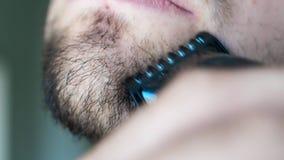 El hombre ascendente cercano afeita la barba en cara con la maquinilla de afeitar negra El hombre sin afeitar utiliza la maquinil almacen de video