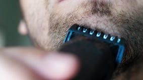 El hombre ascendente cercano afeita la barba en cara con la maquinilla de afeitar negra El hombre sin afeitar utiliza la maquinil almacen de metraje de vídeo