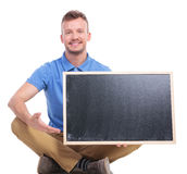 El hombre asentado los jóvenes presenta la pizarra en blanco Foto de archivo libre de regalías