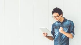 El hombre asiático celebra actitud del éxito, usando la tableta digital, con el espacio de la copia Gente acertada, concepto de l Foto de archivo libre de regalías