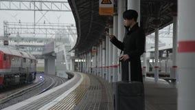 El hombre asiático con la maleta y el teléfono se está colocando en la plataforma ferroviaria almacen de video