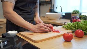 El hombre asiático da el tomate del corte en la tajadera Ciérrese encima del tiro de verduras frescas en la encimera El varón est almacen de metraje de vídeo