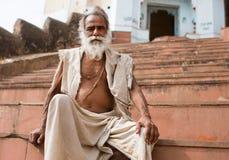 El hombre asiático de la barba blanca se sienta en los pasos de un templ Imagenes de archivo