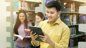 El hombre asiático del adolescente lee una tableta con las muchachas habla en el abucheo Fotografía de archivo libre de regalías