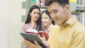 El hombre asiático del adolescente lee una tableta con las muchachas habla en el libro sh Imagen de archivo