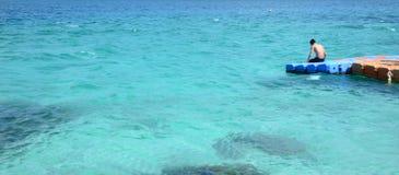 El hombre asiático del adolescente se está sentando en el embarcadero plástico en el mar azul durante Fotos de archivo libres de regalías