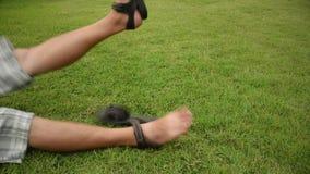 El hombre asiático es que mueve de un tirón y de retroceso con el pie golpeando sus pies en la tierra de la hierba con locura o c almacen de metraje de vídeo