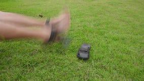 El hombre asiático es que mueve de un tirón y de retroceso con el pie golpeando sus pies en la tierra de la hierba con locura o c metrajes
