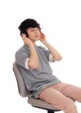 El hombre asiático escucha el teléfono principal Imagen de archivo