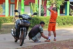 El hombre asiático está atando los zapatos para el hijo imagenes de archivo