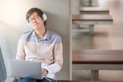 El hombre asiático joven del estudiante goza el escuchar la música Fotos de archivo libres de regalías