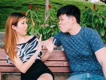 El hombre asiático joven que intenta besar a una muchacha y consigue rechazado Imagenes de archivo