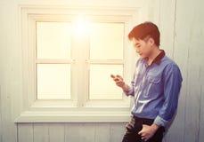 El hombre asiático joven que se coloca que juega el teléfono celular cerca de ventana mira tan Imágenes de archivo libres de regalías