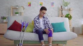 El hombre asiático joven que se sienta en el sofá pone un vendaje elástico de ajuste en una rodilla enferma almacen de video