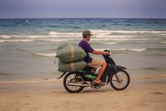 El hombre asiático lleva bolsos grandes en la moto a lo largo de la playa Fotografía de archivo libre de regalías