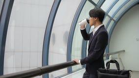 El hombre asiático masculino en chaqueta bebe el café y mira la ventana en la lluvia metrajes