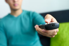 El hombre asiático mira el canal de los cambios de la TV el considerarse teledirigido Fotos de archivo libres de regalías