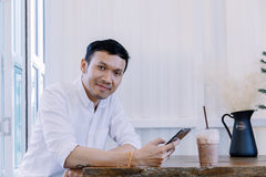 El hombre asiático que usa un teléfono móvil y el café de la bebida en panadería hacen compras Fotografía de archivo