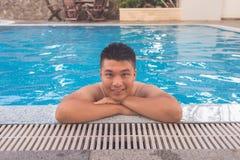 El hombre asiático sonriente disfruta de tiempo libre en piscina Imagen de archivo libre de regalías
