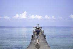 El hombre asiático utilizó las muletas de madera camina en el barco del embarcadero del puente en el mar y el cielo brillante en  fotos de archivo