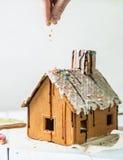 El hombre asperja la aspersión hecha en casa de la confitería de la casa de pan de jengibre Foto de archivo libre de regalías