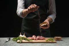 El hombre asperja los prendederos del filete del subordinado con la sal de la pimienta El cocinero trabaja en la cocina abierta d fotografía de archivo libre de regalías