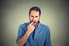 El hombre asqueado con el finger en boca descontentó con la situación lista para lanzar para arriba Imagenes de archivo