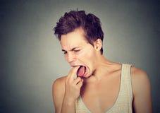 El hombre asqueado con el finger en boca descontentó listo para lanzar para arriba Foto de archivo libre de regalías