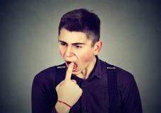 El hombre asqueado con el finger en boca descontentado quiere lanzar para arriba Fotografía de archivo