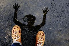 El hombre asustadizo del zombi con sangre caída en los zapatos cría para arriba a Han espeluznante fotos de archivo