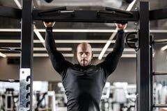 El hombre atlético brutal vestido en ropa negra de las clases levanta en la barra en el gimnasio foto de archivo libre de regalías