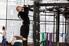 El hombre atlético brutal vestido en ropa negra de las clases levanta en la barra en el gimnasio fotos de archivo